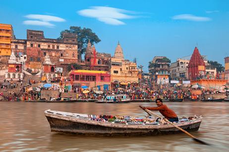 En man ror längs floden Ganges i Indien